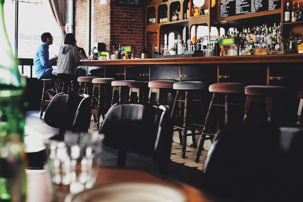 Two people talking at a bar. Talking to customers should be a keystone of any good startup marketing plan.