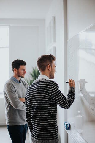 Two men at a whiteboard reviewing data. A live chat widget coupled with a simple CRM can produce actionable data. Photo by Jonathan Velasquez on Unsplash (https://unsplash.com)